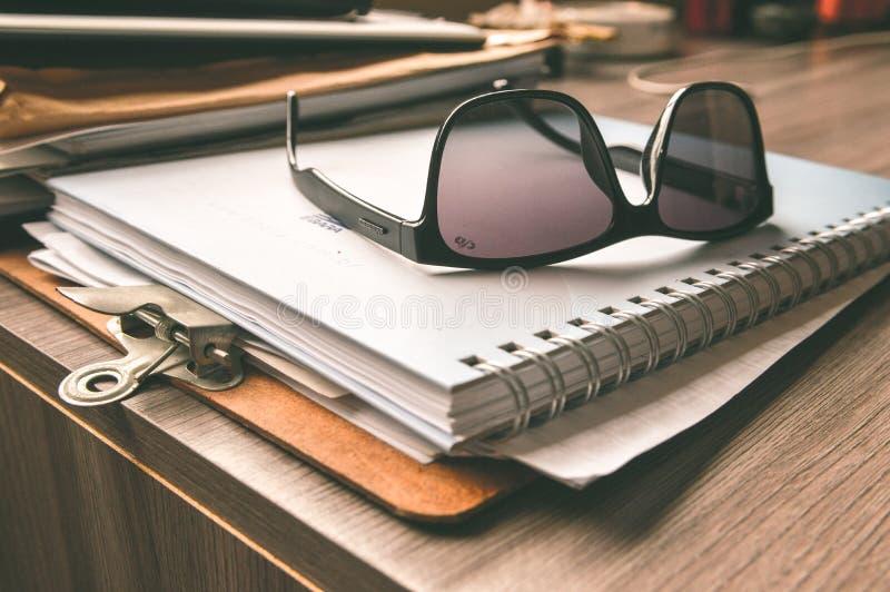 Black Frame Wayfarer Sunglasses on White Notebook stock photography
