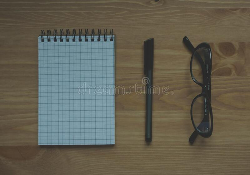 Black Framed Eyeglasses Near Graphing Paper Spiral Notebook royalty free stock photo