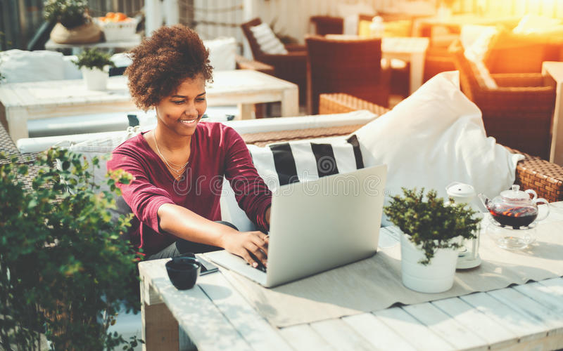 Black freelancer woman with laptop in street bar. Laughing successful young afro american freelancer girl with perfect smile is resolving her work tasks while stock photography