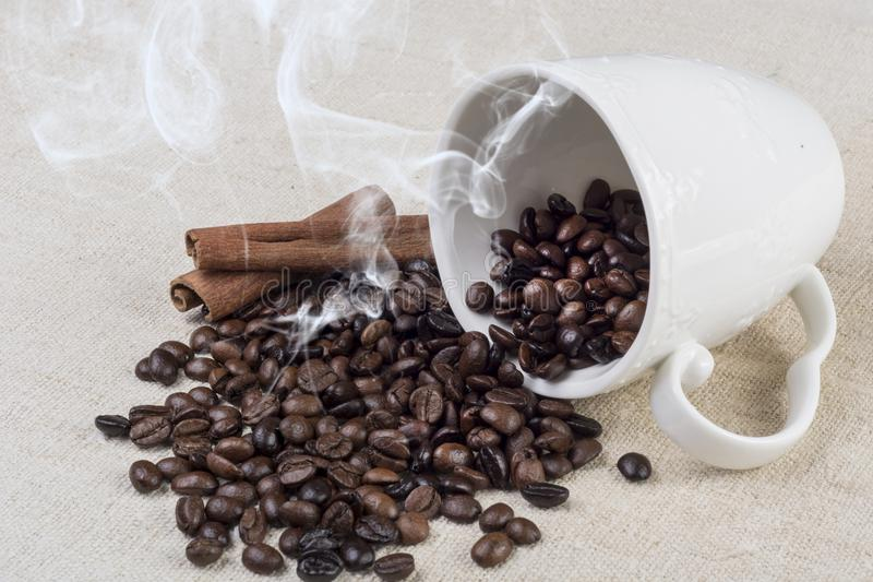 Fresh roasted coffee bean smoke and spilled from coffee cup and cinnamon on retro desk. Black Fresh roasted coffee bean smoke and spilled from white coffee cup stock photos