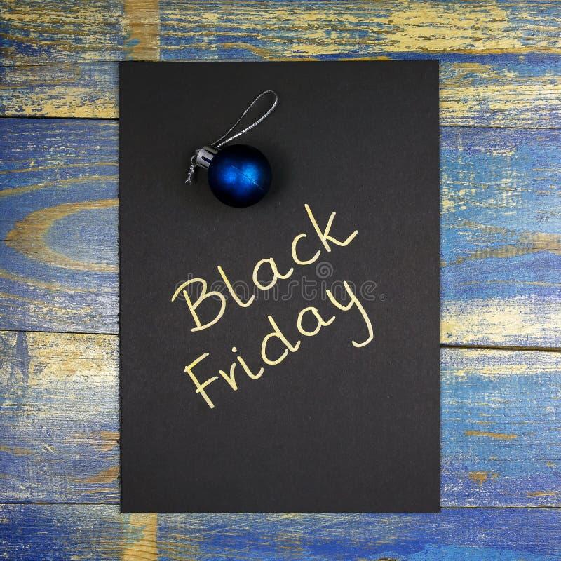 Black Friday écrit sur la carte noire avec la babiole de Noël photos stock