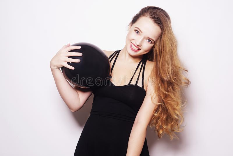 Black friday, a beautiful girl in a black dress with long hair laughs on a white background. The brunette is smiling royalty free stock image