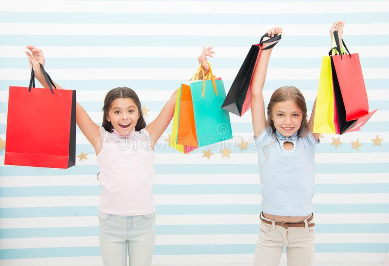 Black friday coming. Kids girls children with packages after shopping day. Girls friends happy carry paper bags. Best royalty free stock photos