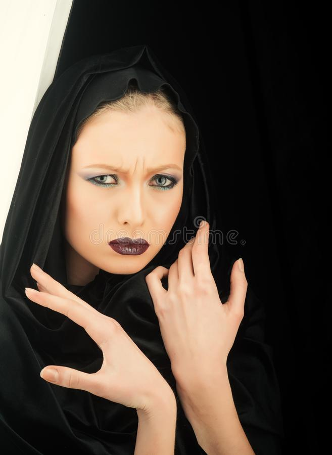 Black Friday concept. Gothic fashion and beauty. Makeup look and skincare sensual of girl. Fashion model with makeup of. Mysterious girl. woman in black hood stock photography