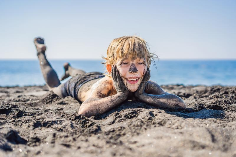 Black Friday concept. Smiling boy with dirty Black face sitting and playing on black sand sea beach before swimming in royalty free stock images