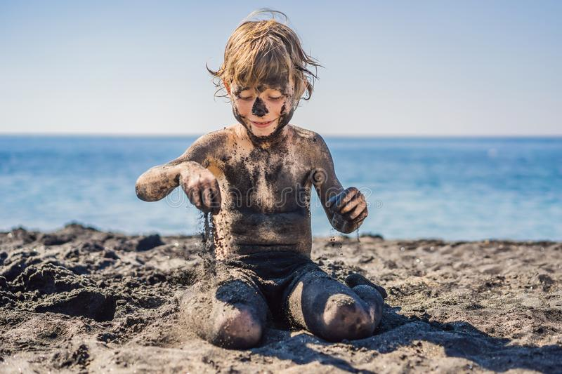 Black Friday concept. Smiling boy with dirty Black face sitting and playing on black sand sea beach before swimming in royalty free stock photo