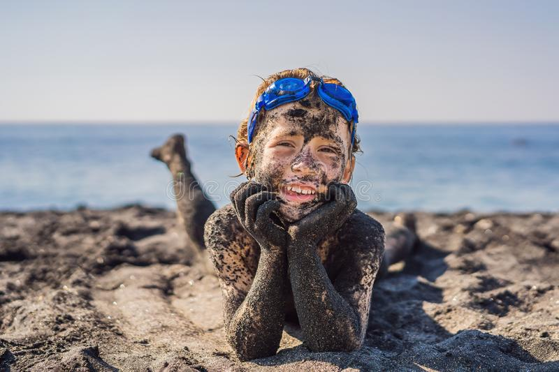 Black Friday concept. Smiling boy with dirty Black face sitting and playing on black sand sea beach before swimming in royalty free stock image