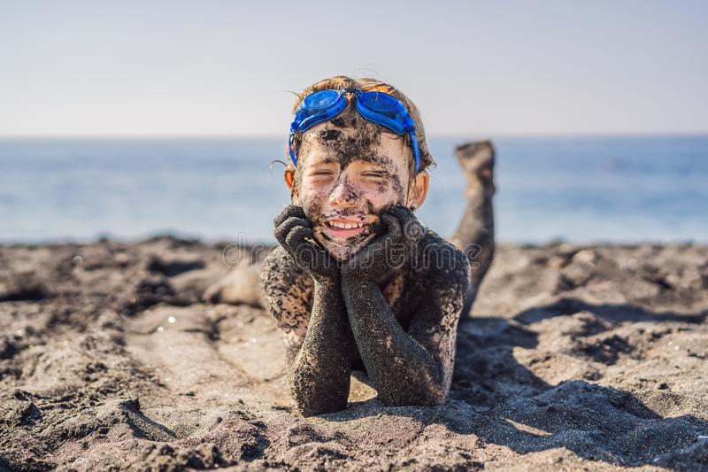 Black Friday concept. Smiling boy with dirty Black face sitting and playing on black sand sea beach before swimming in stock images