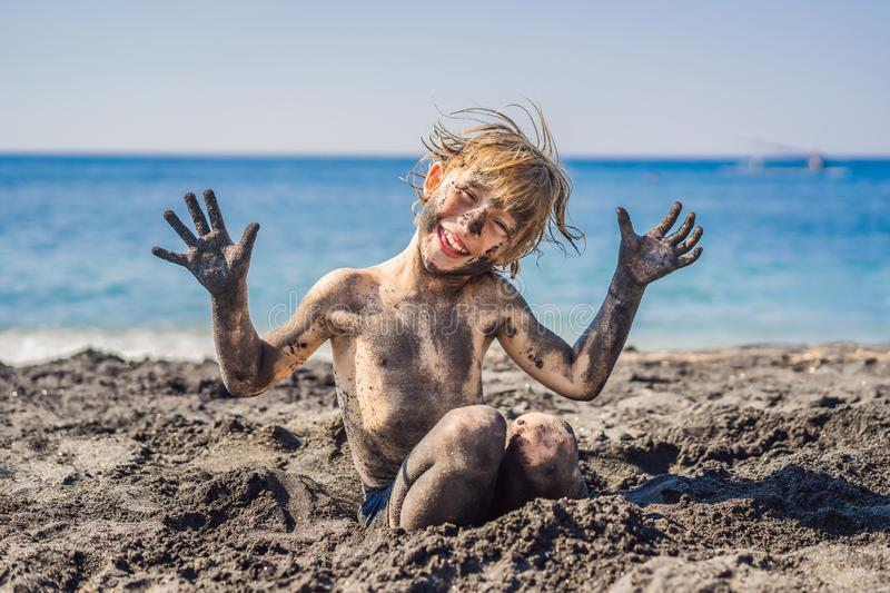 Black Friday concept. Smiling boy with dirty Black face sitting and playing on black sand sea beach before swimming in stock photography