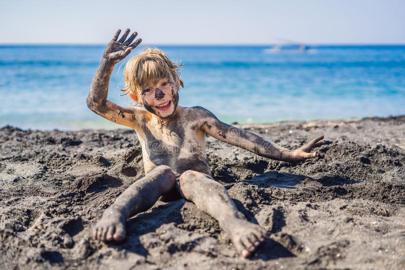 Black Friday concept. Smiling boy with dirty Black face sitting and playing on black sand sea beach before swimming in stock image