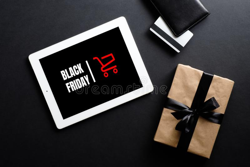 Black friday discount concept. Flat lay tablet with sign. `Black friday`, gift box, credit card over black background royalty free stock photo