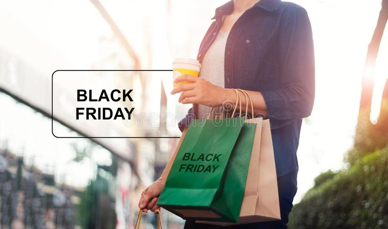 Black Friday, femme avec la tasse de café tenant des sacs à provisions images libres de droits