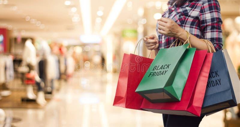 Black Friday, femme tenant des paniers marchant dans le mail photographie stock