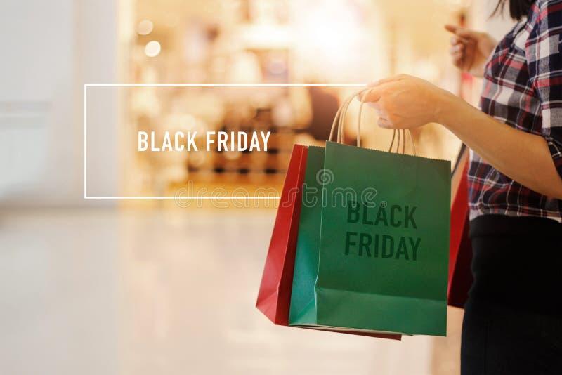 Black Friday, femme tenant des paniers marchant dans le mail image stock