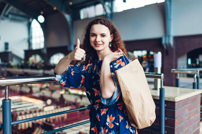 Black friday. Happy woman holding shopping paper bag in shopping center and showing thumb up. Purchases royalty free stock images