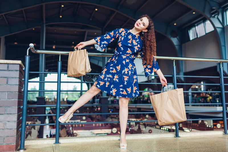Black friday. Happy woman holding shopping paper bags in shopping center and having fun. Purchases stock images