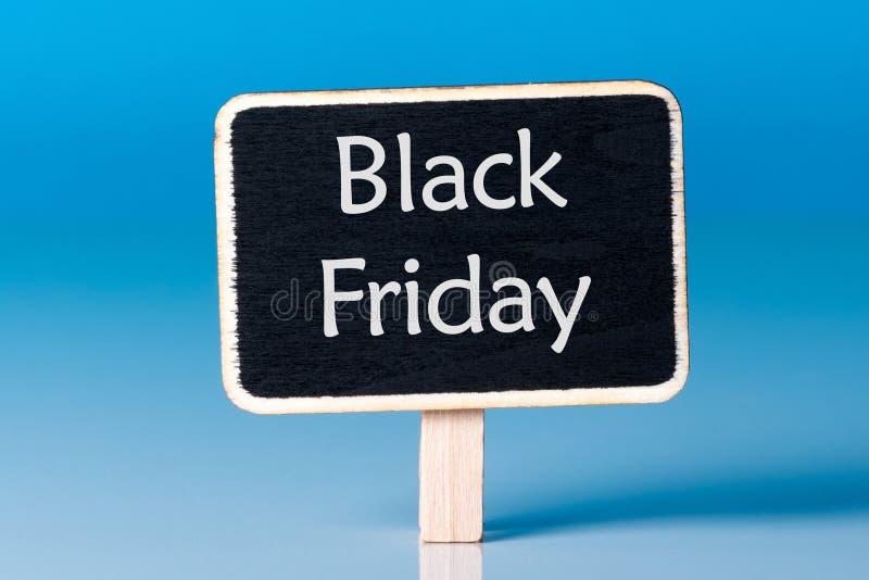 Black Friday-het winkelen verkoopconcept met weinig houten markering Dichte omhooggaand van de verkoopmarkering op blauwe achterg stock foto's