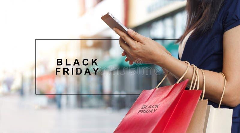 Black Friday, kobieta używa smartphone przewożenia torba na zakupy obrazy stock