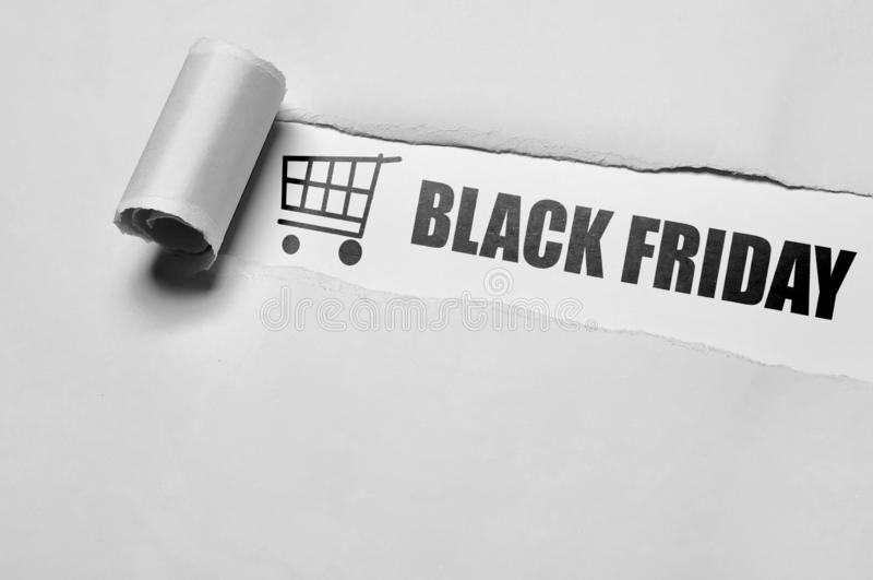 Black Friday message appering behind ripped paper royalty free stock image
