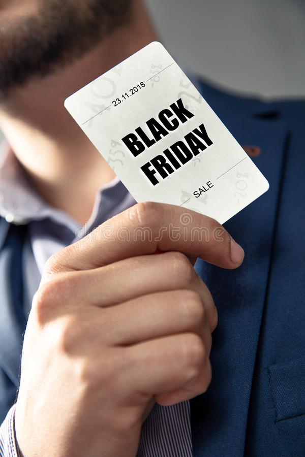 Black Friday`s Sale card holded by an elegant man in suit. Conception of Black Friday`s sales and discounts at shops royalty free stock images
