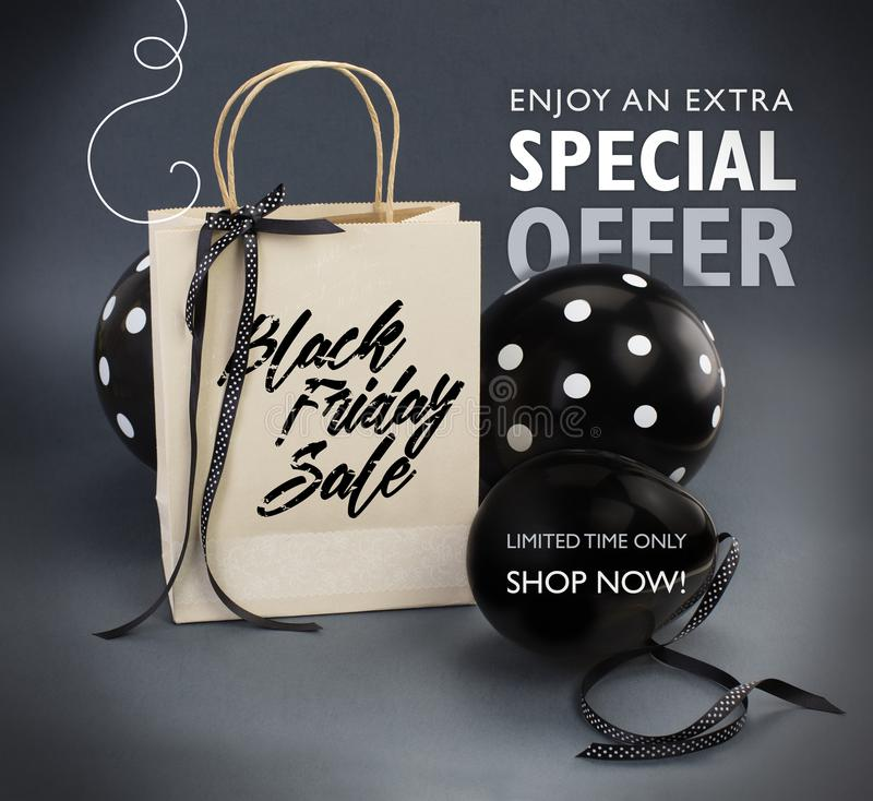 Black Friday sale banner containing recycled paper bag decorated with black satin ribbon, and black balloons. stock images