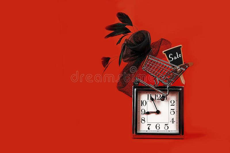 Black Friday sale concept with silver clock, shopping cart with sign sale and female hat retro style on red background. Time planning, copy space. Party royalty free stock photos
