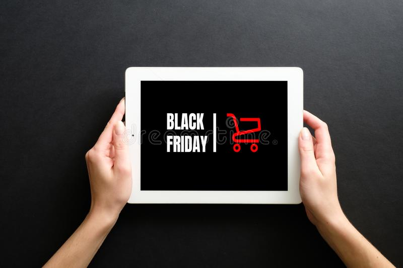 Black friday sale concept. Woman`s hands holding tablet pad with sign `Black friday` and shopping cart.  stock image