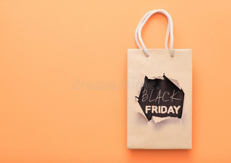 Black friday sale seasonal discount shopping bag. Black friday sale. Seasonal discount. Paper shopping bag. Orange background royalty free stock photo