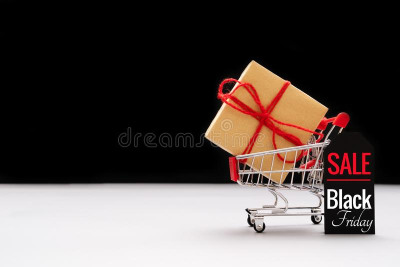 Black Friday sale, shopping cart and gift box with price tag royalty free stock image