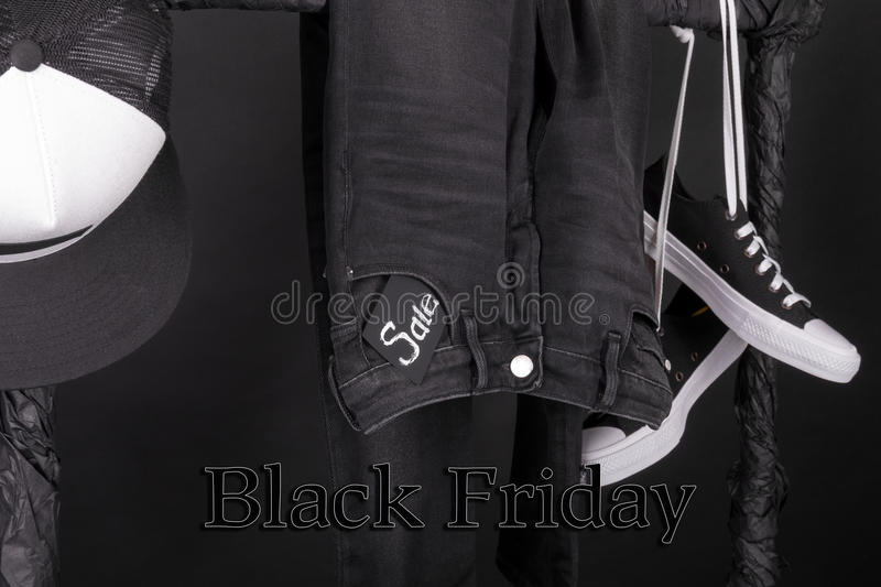 Black friday. Sale sign. and white snaekers, cap pant, jeans hanging on clothes rack background. Close up. Black friday. Sale sign. Black and white snaekers stock image