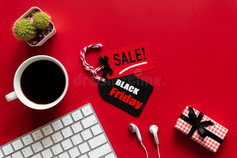 Black Friday Sale text on a red and black tag with coffee cup. Keyboard computer and gift box on red background. Shopping concept royalty free stock photos