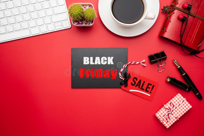 Black Friday Sale text on a red and black tag with coffee cup, plant table, gift box Earphone and mouse keyboard on red background. Shopping concept royalty free stock photos