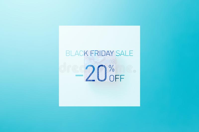 Black friday sale. Up to 20% discount. Text over Blue gift box with blue ribbon on blue background. Word BLACK FRIDAY on blue background. Flat lay. Minimal stock image