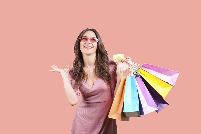 Black friday season sale concept. Attractive young woman with long brunette hair, wearing tight dress, holding many different royalty free stock images