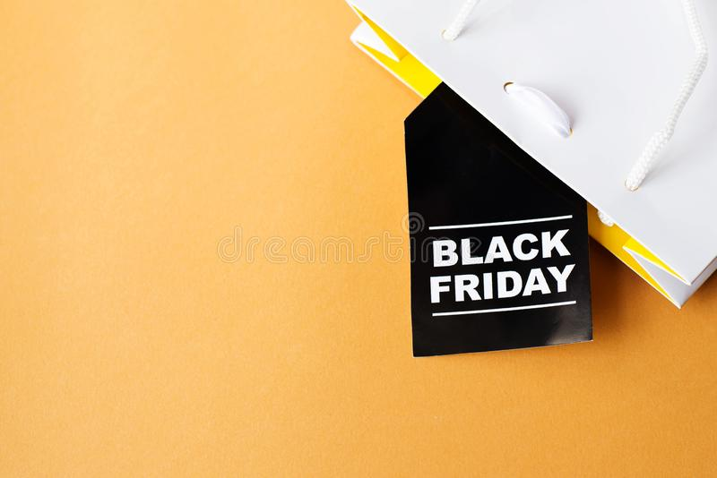 Black Friday shopping bag on yellow background. Copy space royalty free stock image
