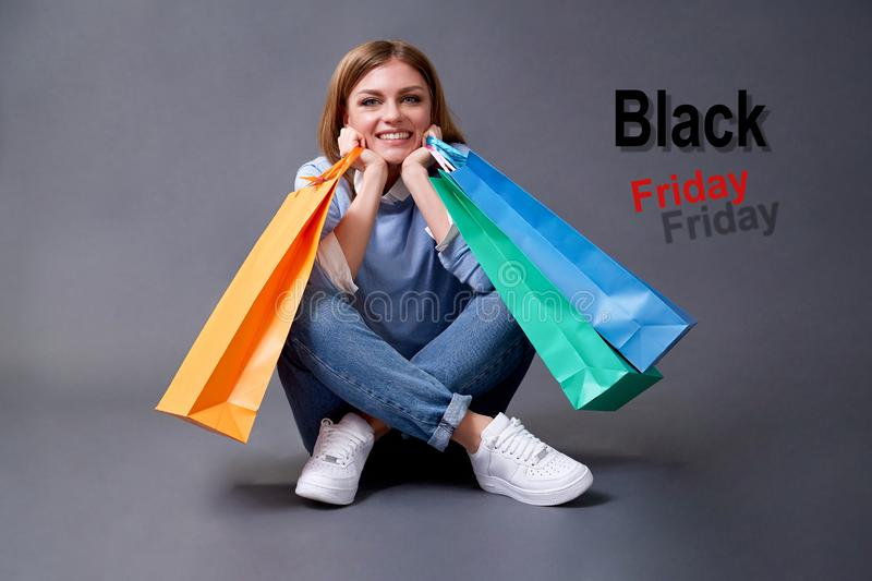 Black Friday, Shopping and commerce concept. Portrait of girl with bag sitting on the floor. stock images