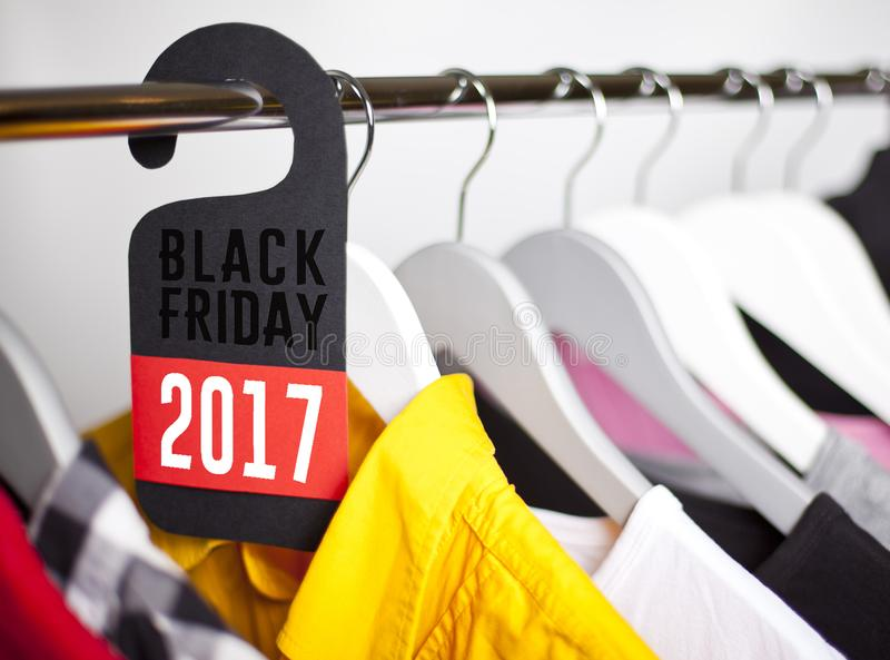 Black Friday shopping sale concept. Sale in a clothing store - discount sign at a clothes rack stock images