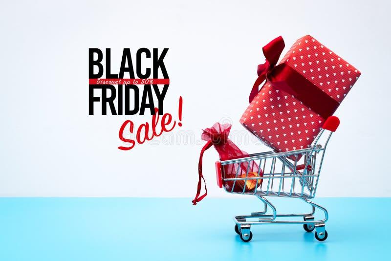 Black Friday sprzedaż, wózek na zakupy i prezenta pudełko z kieszeniowym pieniądze, obrazy royalty free