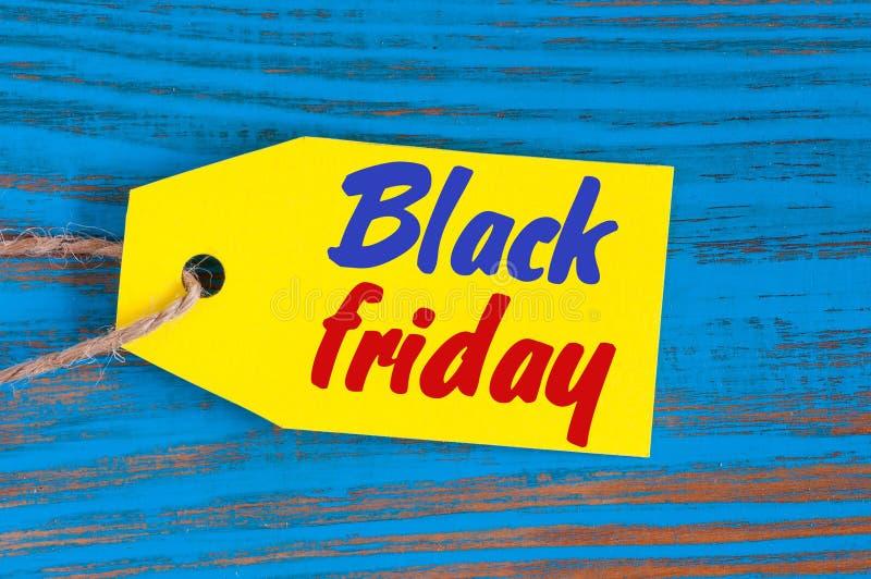 Black Friday sprzedaży etykietka na błękitnym drewnianym tle Sprzedaż, rabat, reklama, marketingowe metki dla odziewa zdjęcia stock