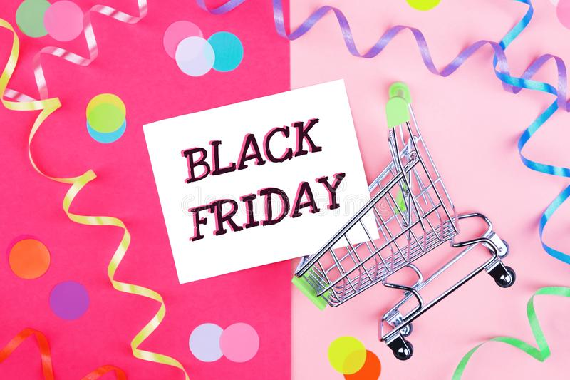 Black Friday text in carriage on bright desk. Black Friday text in a shopping carriage on a bright background with multi-colored confetti stock photography