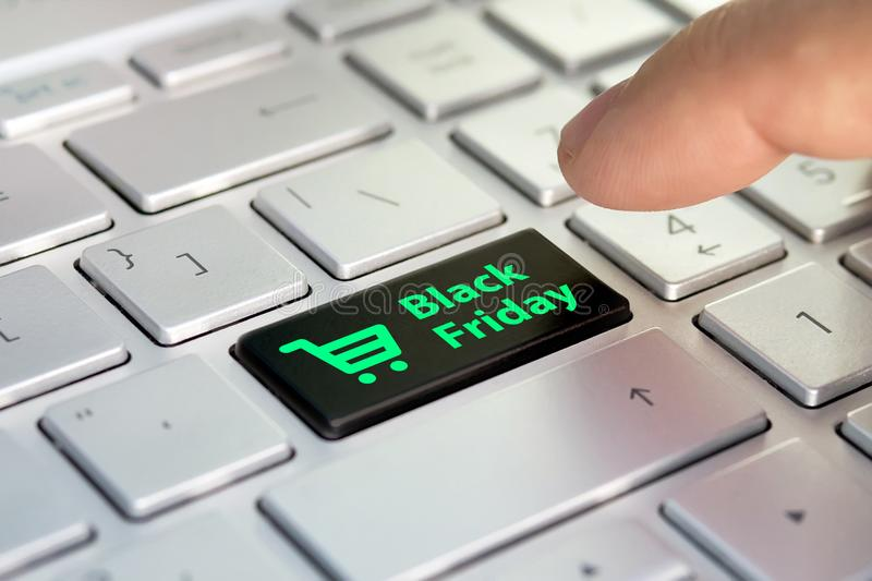 Black friday text and shopping cart on keyboard. Black friday concept. black button on the gray silver keyboard of modern ultraboo royalty free stock image