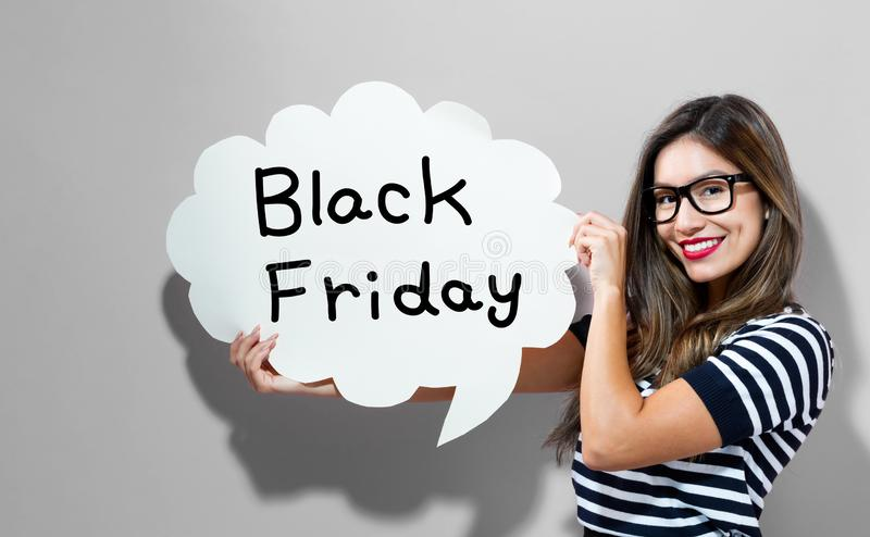Black Friday text with woman holding a speech bubble. Black Friday text with young woman holding a speech bubble royalty free stock images
