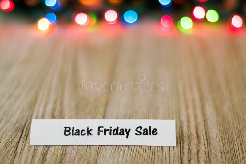 Black Friday-Verkoopconcept op houten raad en gekleurde lichten, selectieve nadruk, ruimte voor exemplaar stock fotografie