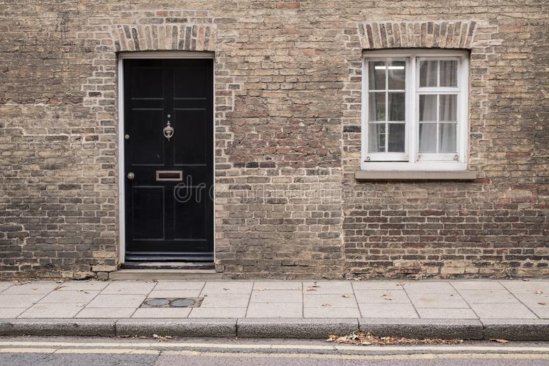 Black front door on a restored brick wall of a Victorian house residential building royalty free stock images