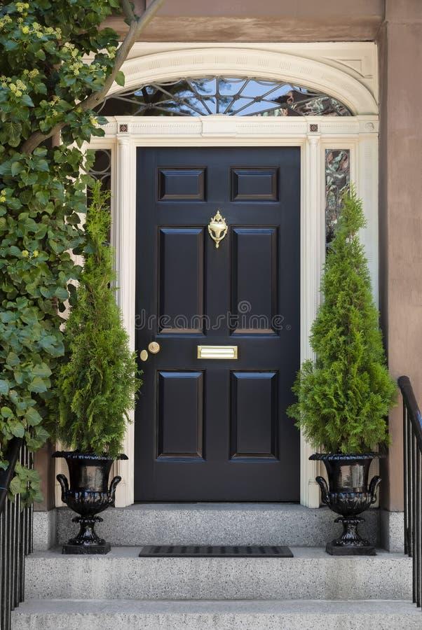 Black Front Door With White Door Frame And Greenery Stock