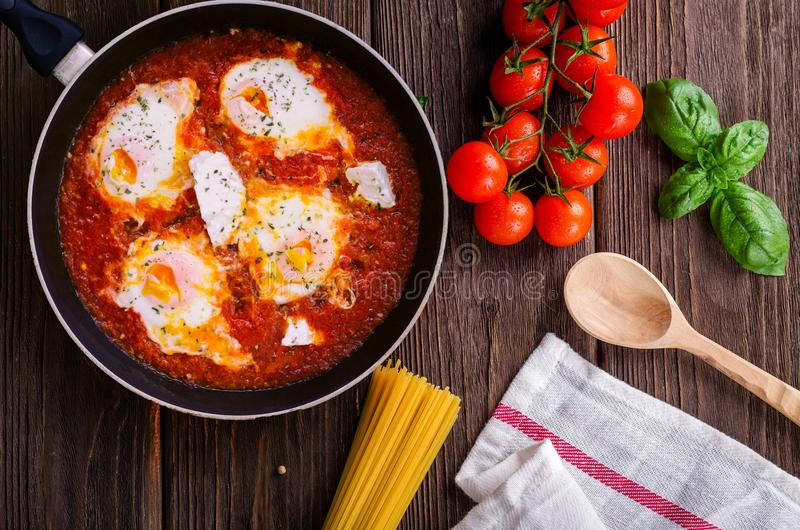 Black Frying Pan With Spaghetti Sauce Near Brown Wooden Ladle and Ripe Tomatoes stock photo