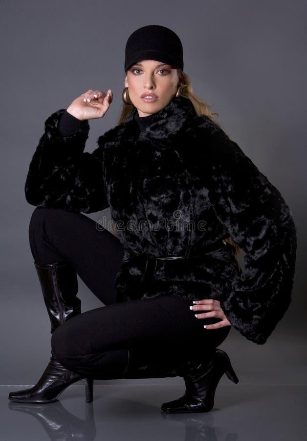 Black fur coat. Pretty model wearing black fur coat and black pants stock photos