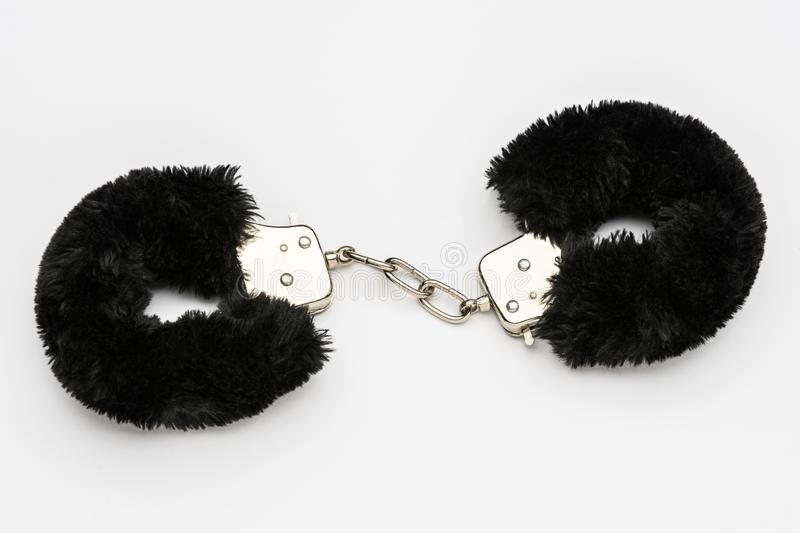 Black furry handcuffs on white background royalty free stock photo