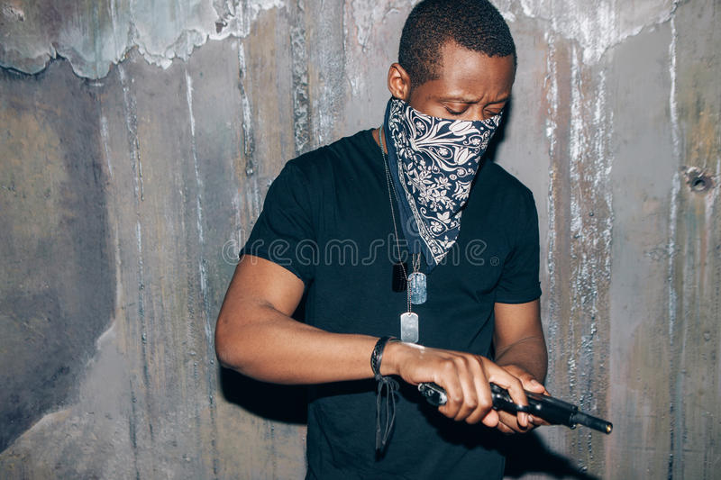 Black gang member checks his weapon. Gangster man with gun in hand on dark gray background. Outlaw, ghetto, murderer, armed attack concept stock photos