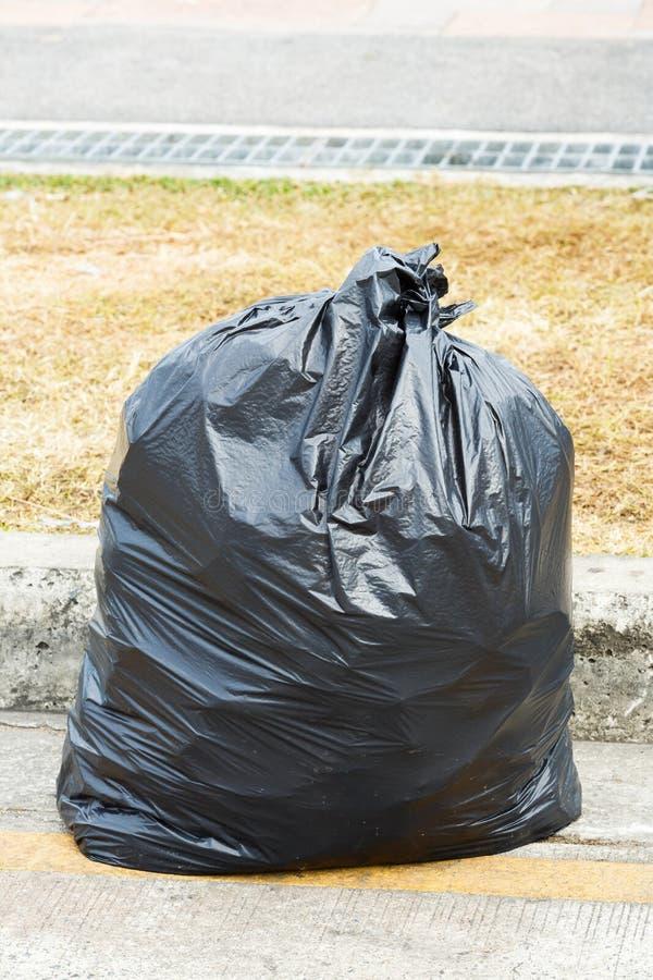 Black garbage bag. Close up black garbage bag with waste inside on concrete floor royalty free stock images